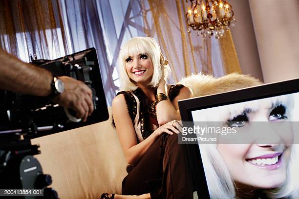 Young woman sitting on sofa, image on screen in foreground