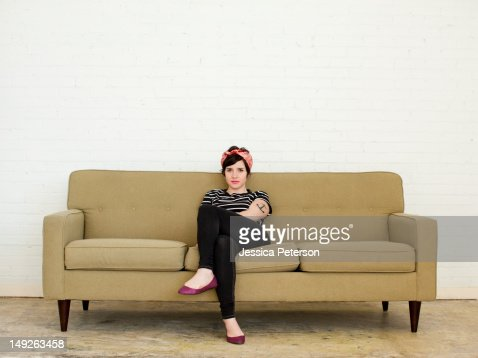 young woman sitting on sofa stock photo getty images. Black Bedroom Furniture Sets. Home Design Ideas