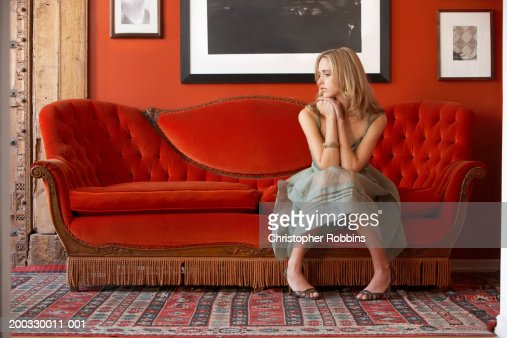 Young woman sitting on sofa, resting elbows on knees, looking to side : Stock Photo