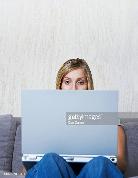 Young woman sitting on sofa using laptop, close-up