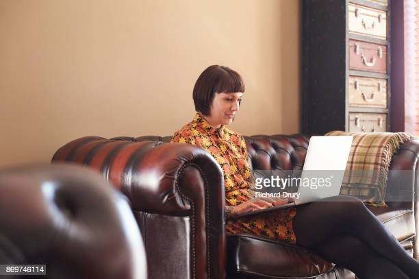 Young woman sitting on sofa using laptop