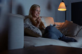 Young woman sitting on sofa, watching tv, eating chocolate