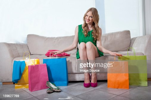 Young woman sitting on sofa with shopping bags : Foto de stock