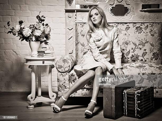 Giovane donna seduta sul divano con le valigie