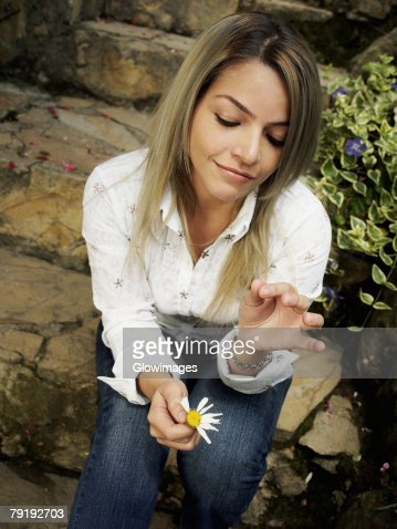 Young woman sitting on steps and picking petals of a flower : Foto de stock