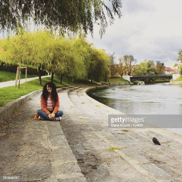 Young Woman Sitting On Steps By Lake At Park