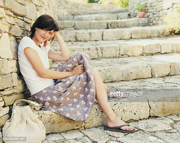 Young woman sitting on steps, head resting on hand, smiling, portrait