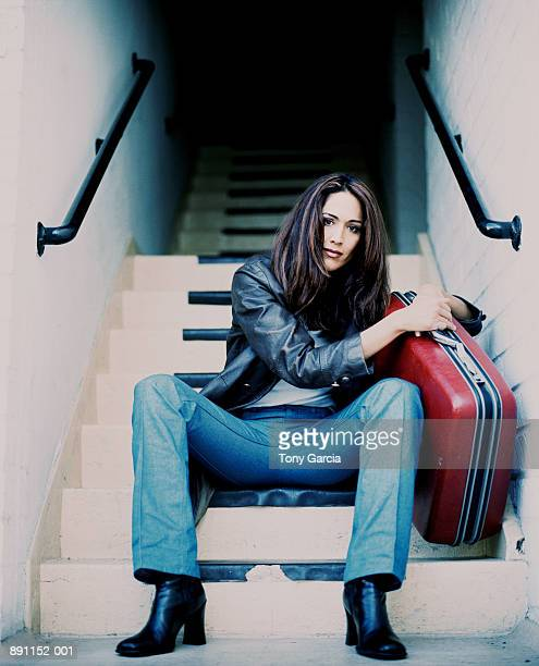 Young woman sitting on steps with suitcase