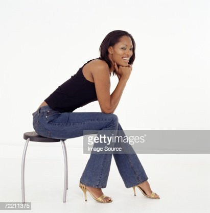 Young Woman Sitting On Stool Stock Photo Getty Images