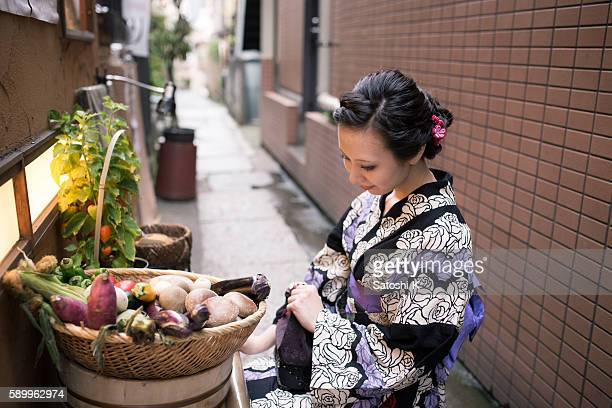 Young woman sitting on street and looking at vegetables