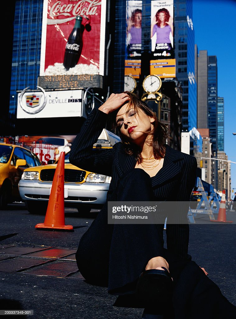 Young woman sitting on street, hand in hair : Stock Photo