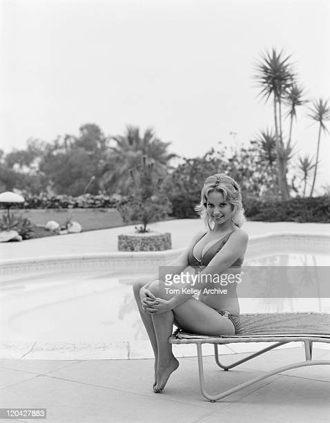 Young woman sitting on sun lounger by swimming pool, smiling, portrait