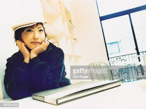 Young woman sitting on table in room, book on table : Stock Photo
