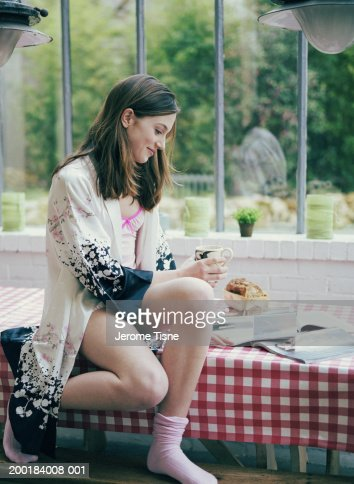 Young woman sitting on table, reading magazines : Stock Photo