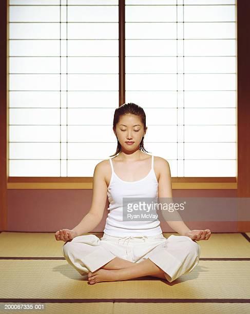 座る若い女性畳、瞑想、目を閉じた