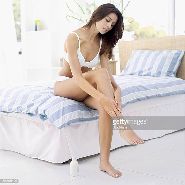 young woman sitting on the bed applying moisturizer on her leg