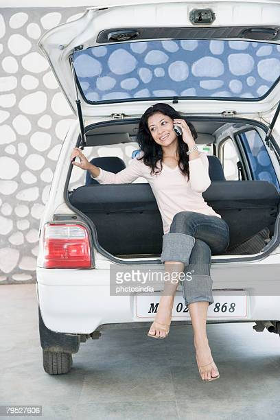 Young woman sitting on the boot of a car and talking on a mobile phone