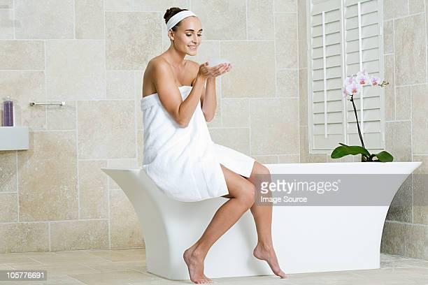 Mujer joven sentada en el borde de la bañera