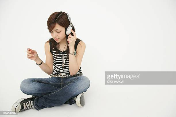 Young woman sitting on the floor and listening to music