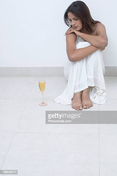 Young woman sitting on the floor beside a champagne flute