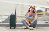 Woman sitting on the floor with crossed legs and listening to music, waiting her flight