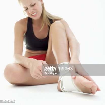 young woman sitting on the floor touching her bandaged foot