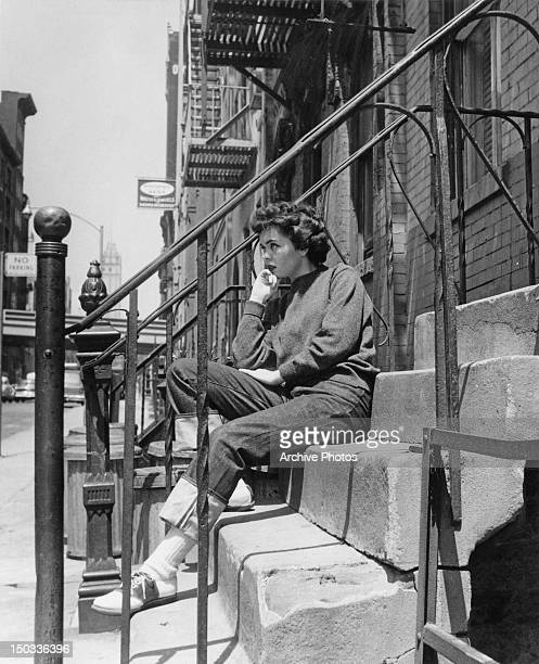A young woman sitting on the front steps of a building circa 1955 She is wearing turnedup denim jeans and bowling shoes
