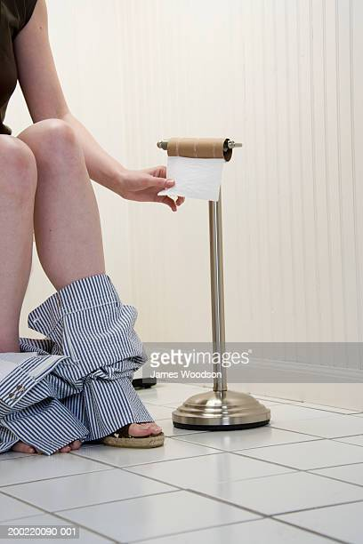Young woman sitting on toilet, by empty loo roll, low section