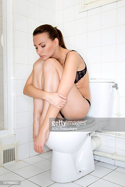 Young woman sitting on toilet