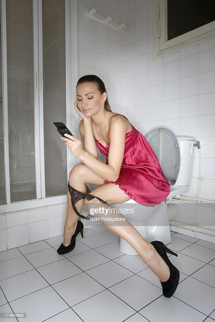 Young Woman Sitting On Toilet Using Phone Stock Photo