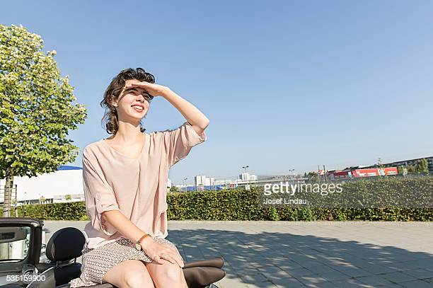 Young woman sitting on top of car