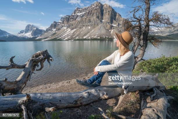 Young woman sitting on tree trunk at mountain lake
