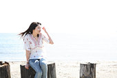 Young Woman Sitting on Trunk at Beach, High Key