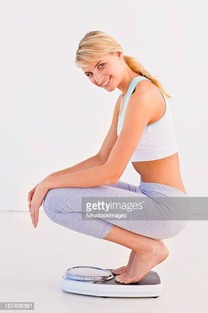 Young woman sitting on weighing machine