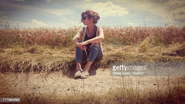 Young Woman Sitting On Wheat Field Against Sky
