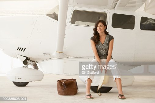 Young woman sitting on wheel of private plane