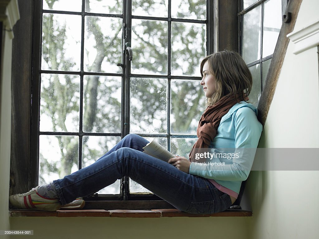 Young Woman Sitting On Window Sill Looking Out Side View