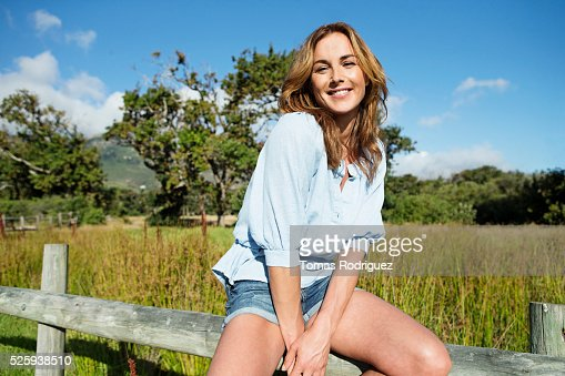 Young woman sitting on wooden fence : Stock-Foto