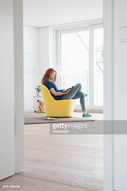 Young woman sitting on yellow armchair in her living room