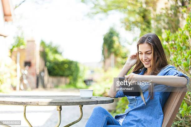 Young woman sitting outdoors and reading a e-book