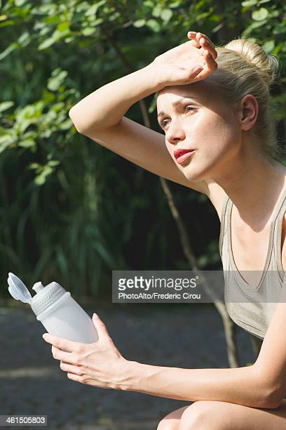 Young woman sitting outdoors with water bottle, wiping forehead with back of hand