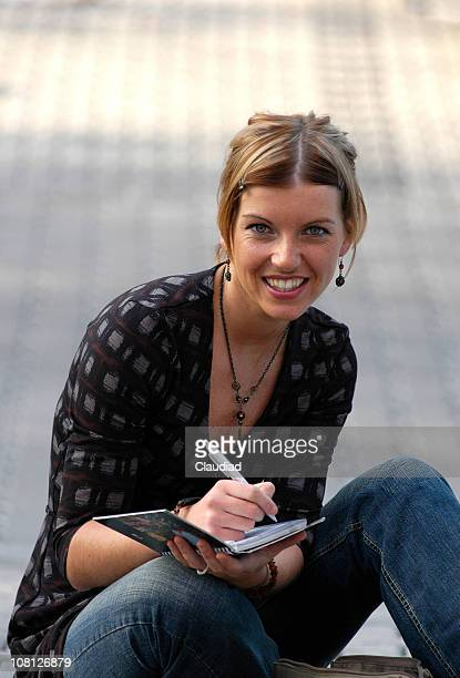 Young Woman Sitting Outside and Writing in Book