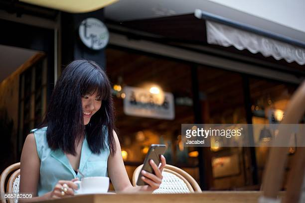 Young woman, sitting outside cafe, using smartphone, Shanghai, China