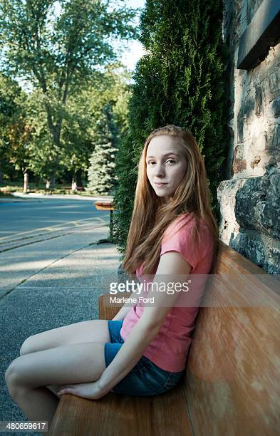 Young woman sitting outside on a bench waiting