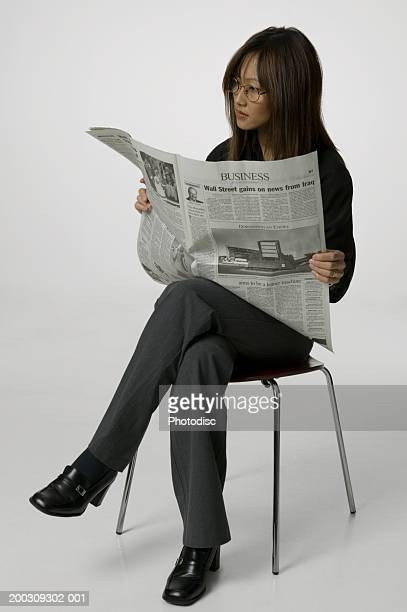 Young woman sitting reading newspaper, posing in studio, portrait