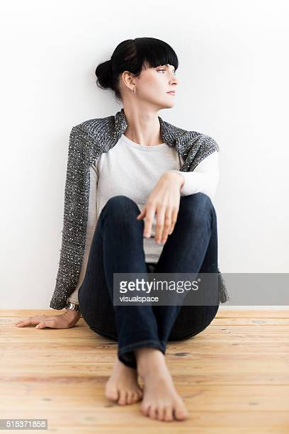 Young Woman Sitting Relaxed On Wooden Floor