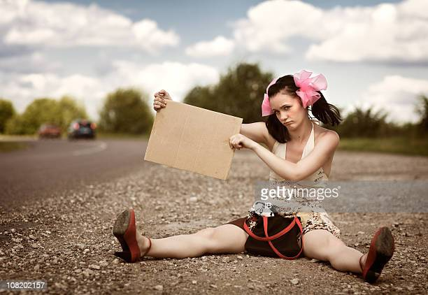 Young Woman Sitting Roadside Holding Blank Sign