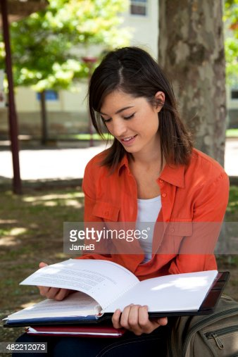 Young woman sitting under a tree reading a book : Stock Photo