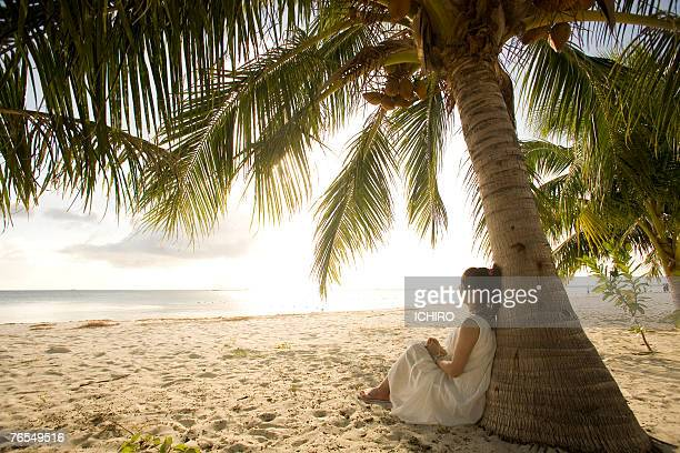Young woman sitting under palm tree on beach
