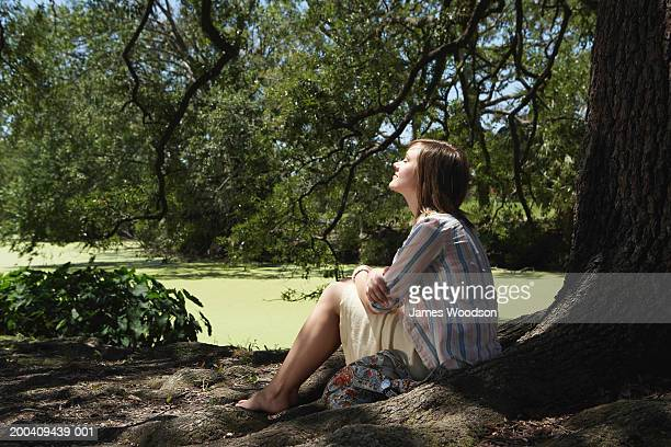 Young woman sitting under tree in park, smiling, side view